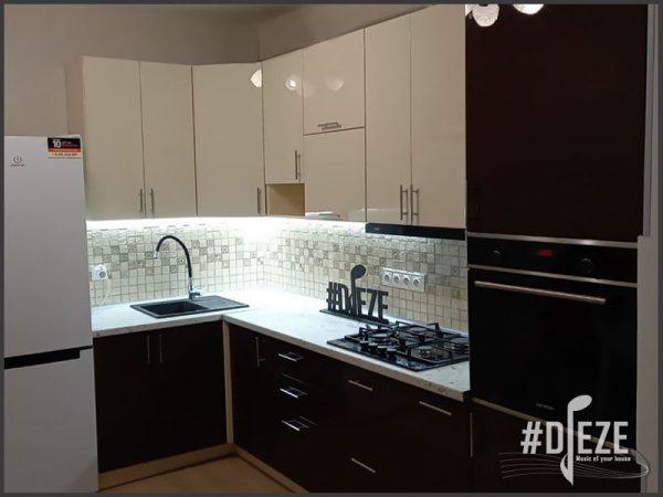 Кухня угловая с высокими верхними модулями и пеналом по правую сторону с уховкой. Верхние шкафчики бежевые глянцевые нижние шкафчики и пенал шоколадноо цвета глянцевые